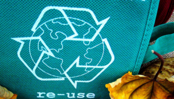 portada con logo de reciclaje impreso en bolsa de tela, hojas de árbol secas y otros